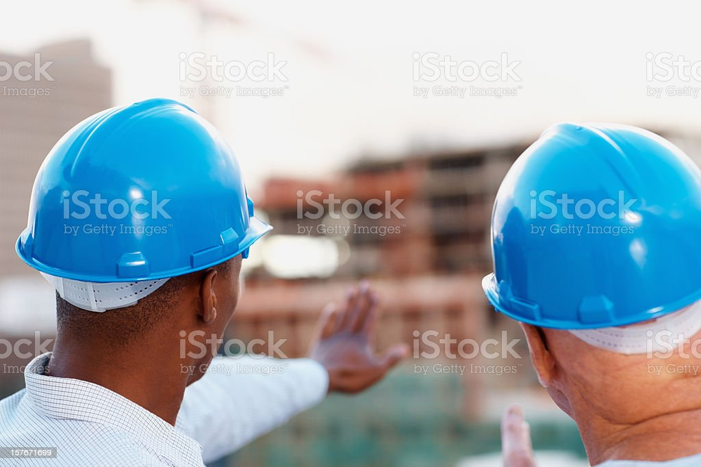 Two architects wearing blue helmet while working together royalty-free stock photo