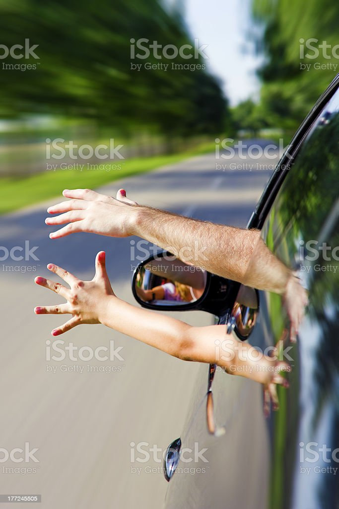 Two arms sticking out of the car stock photo