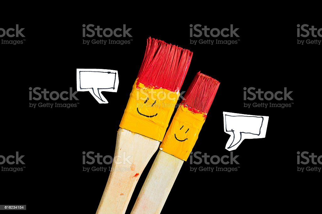 Two art brsushes with smile face talking. stock photo