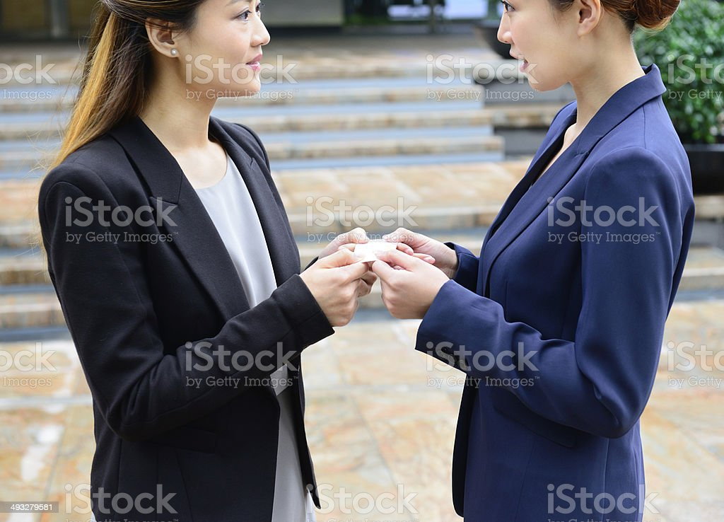 Two asian business women talking, handing over businesscard stock photo