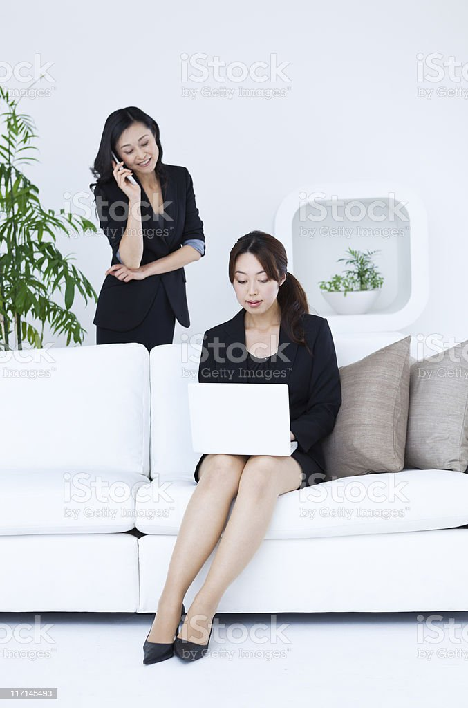 Two Asian Business Women Using Mobile Phone and Laptop Computer royalty-free stock photo
