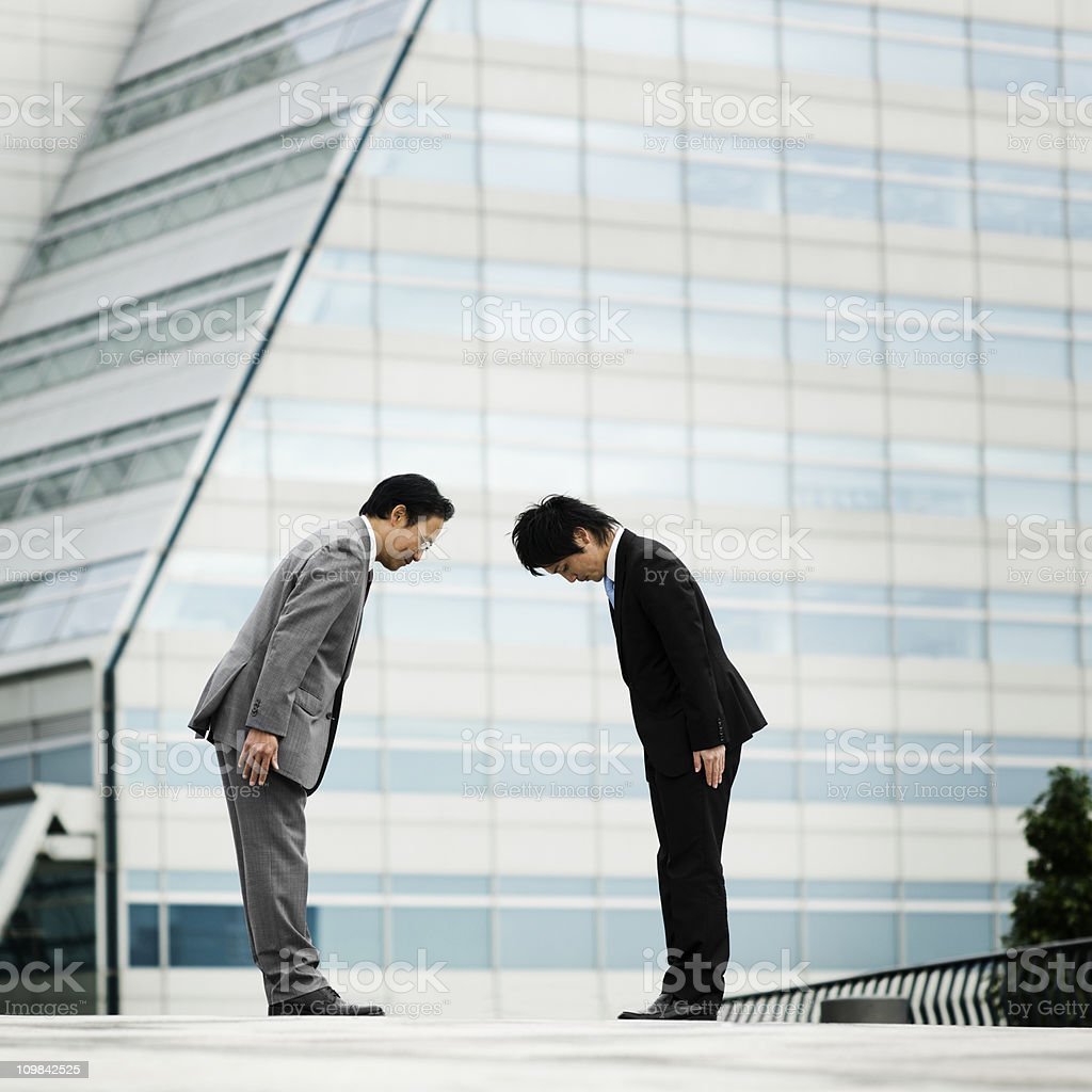 Two Asian Businessmen Bowing stock photo
