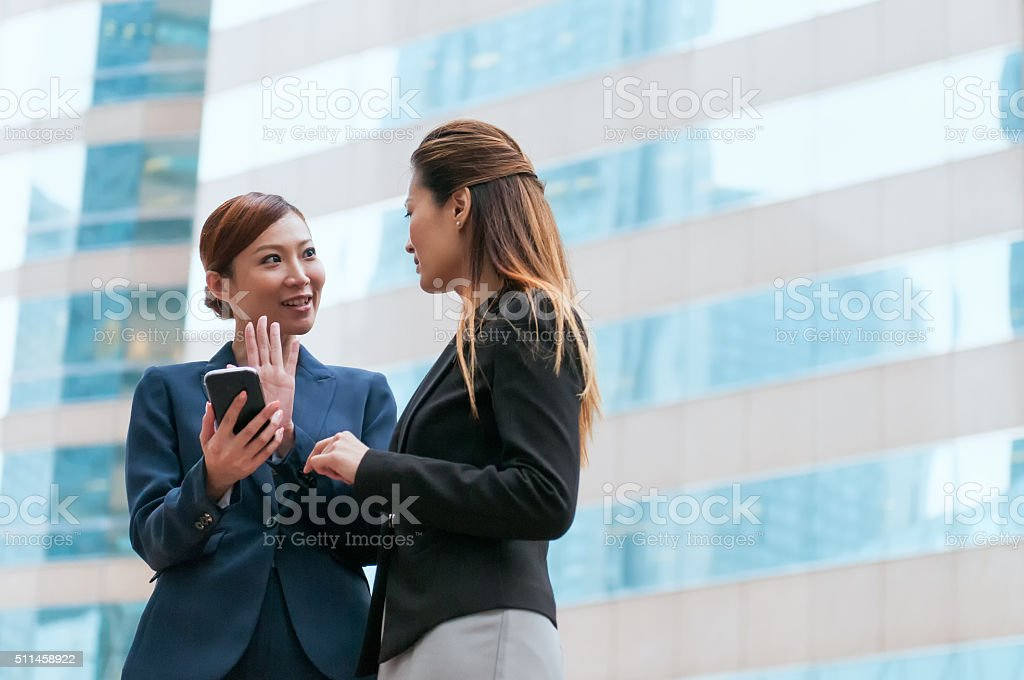 Two Asian Businesswomen in Discussion with Smartphone Outside Office Building stock photo