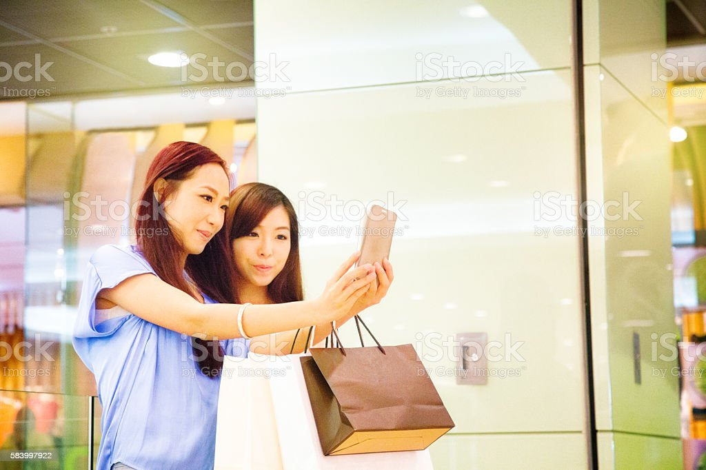 Two asian girls interrupt shopping to play AR game stock photo