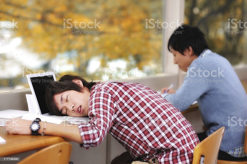 Two Asian students studying but one has fallen asleep royalty-free stock photo