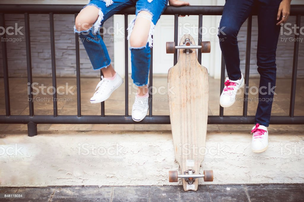 Two Asian young woman smiling happy with skateboard in park; Asian friends are playing long board. stock photo
