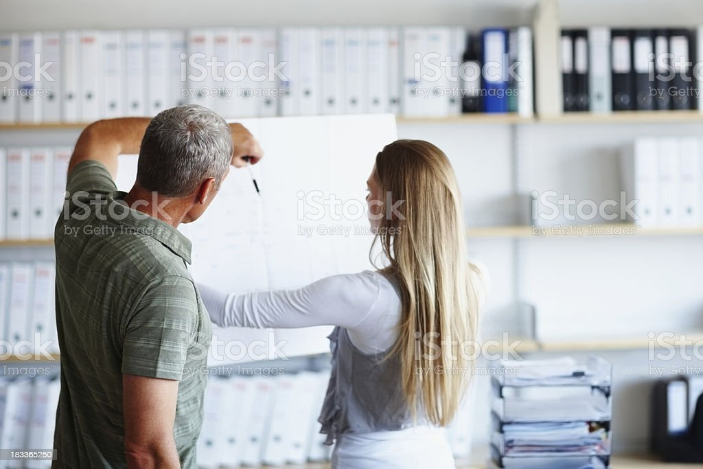 Two associates looking and pointing at blueprint royalty-free stock photo