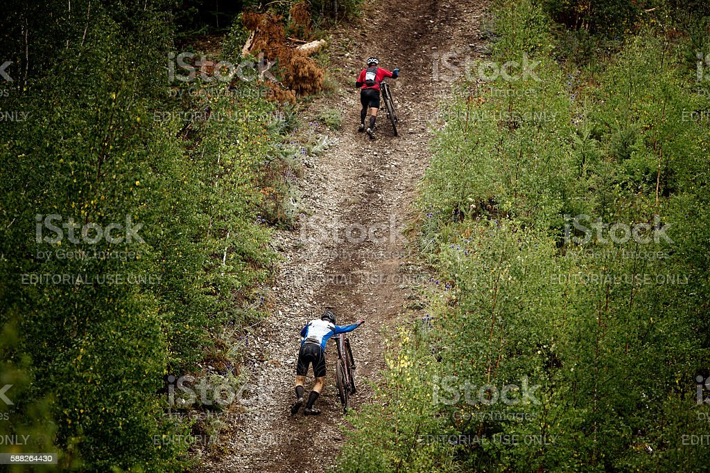 two athlete mountainbiker walking with bicycle uphil royalty-free 스톡 사진
