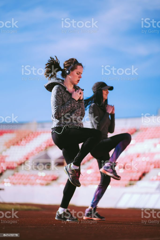 Two Athlete Women Running In a Spot, Doing High Knees Exercise stock photo