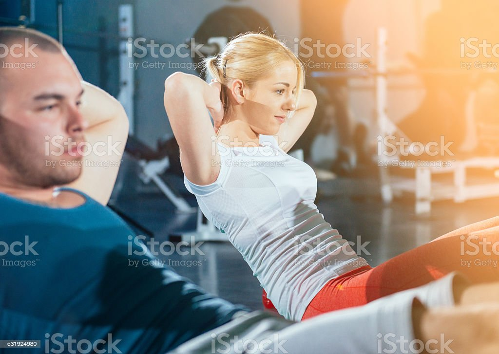 Two athletes doing sit ups for abdominal muscles in gym stock photo