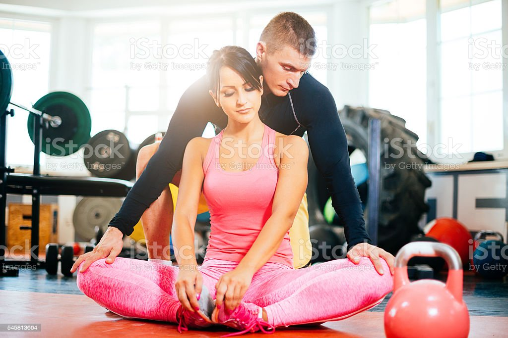Two athletes in gym exercising and stretching  together stock photo