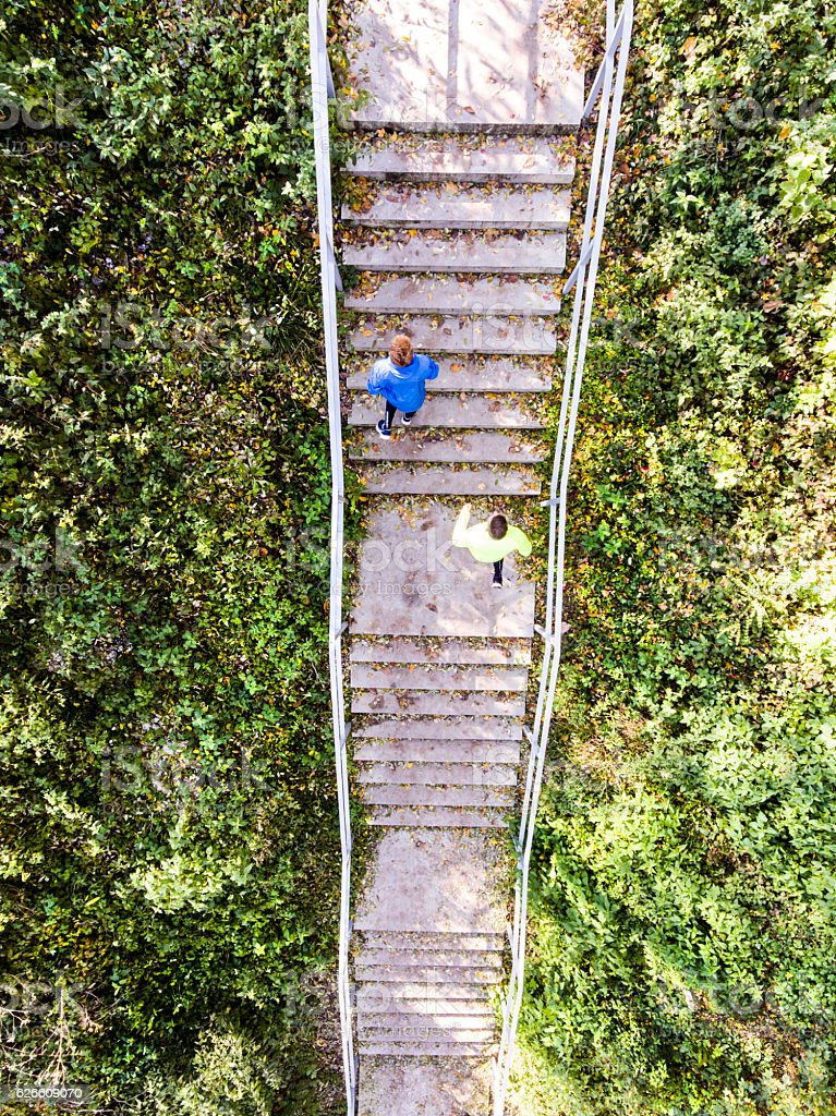 Two athletes running on stairs in sunny nature. Aerial view. stock photo
