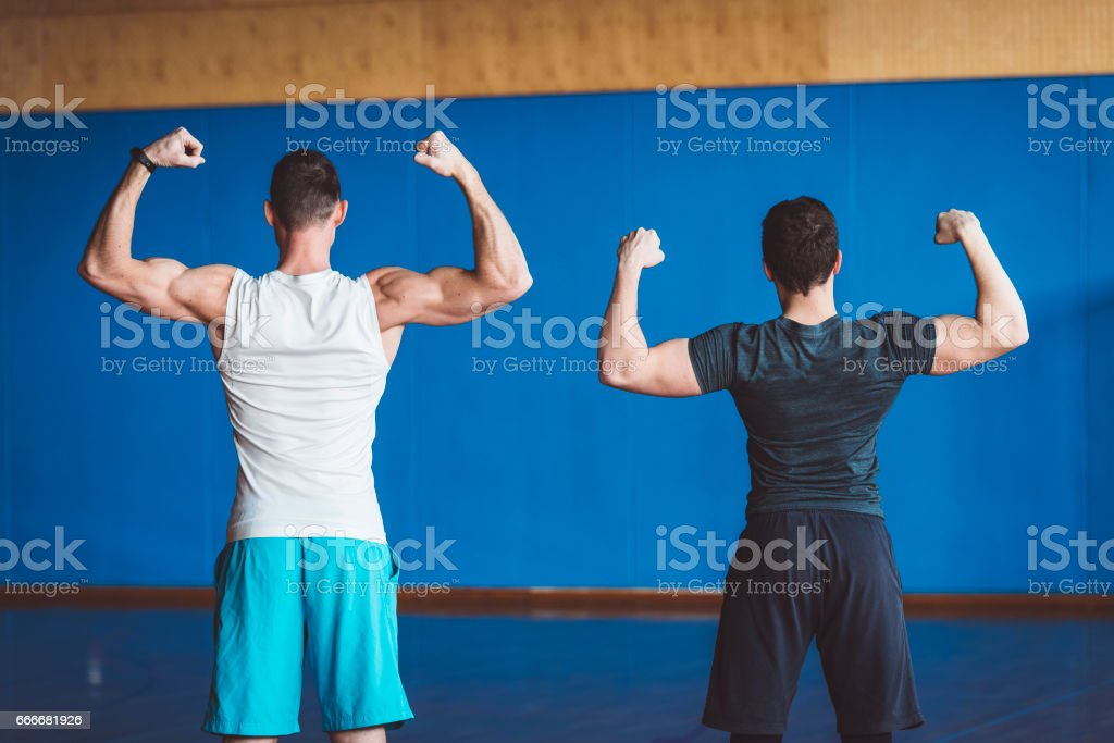 Two athletic guys showing biceps from behind stock photo