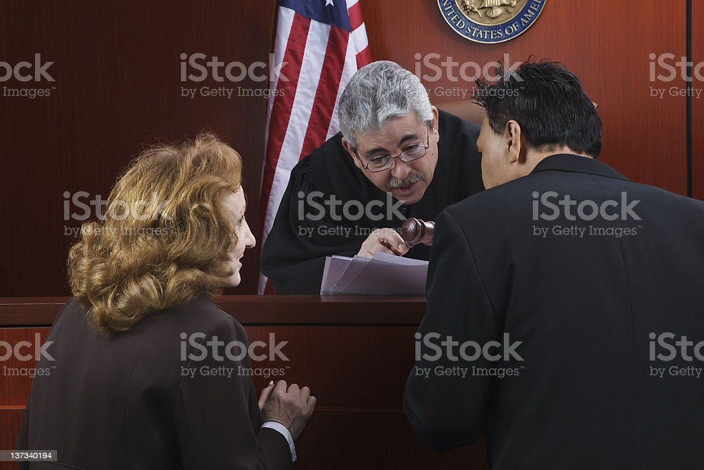 Two attorneys speaking with the judge in the courtroom stock photo