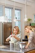 Two attractive blonde female friends baking in stylish european kitchen