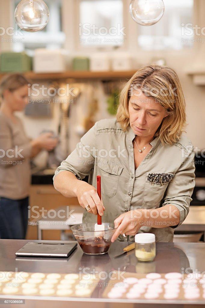 Two attractive blonde female friends baking in stylish european kitchen stock photo