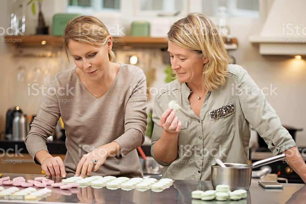 Two attractive blonde female friends baking in stylish european kitchen stock photo