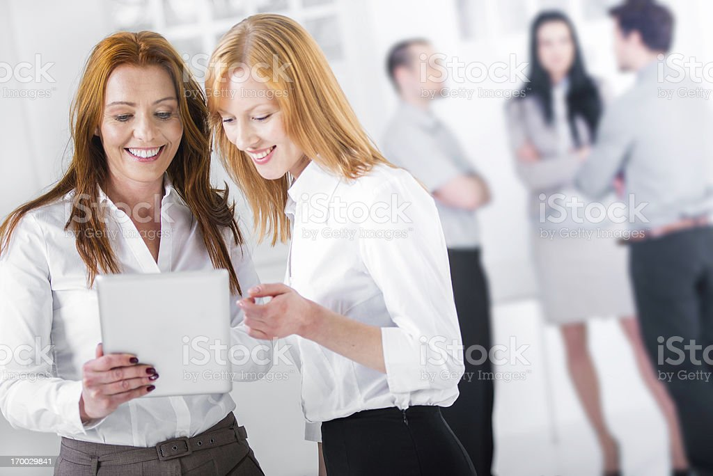 Two attractive businesswomen with digital tablet royalty-free stock photo