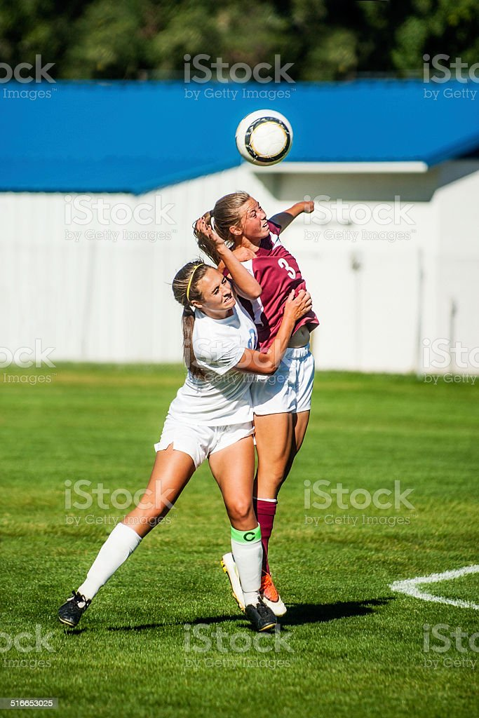 Two Attractive Female Soccer Players Engage in Header Battle stock photo