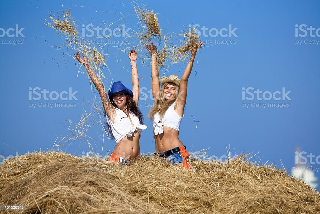 Two attractive girls playing in haystack royalty-free stock photo
