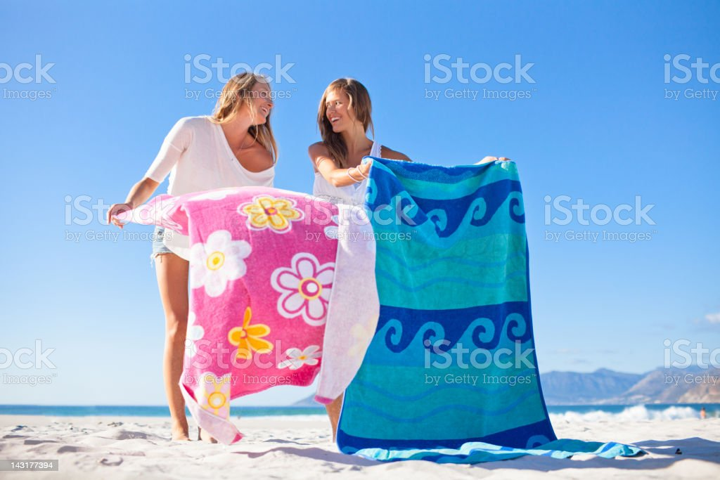 Two attractive teenage girls relaxing and gossiping on the beach royalty-free stock photo