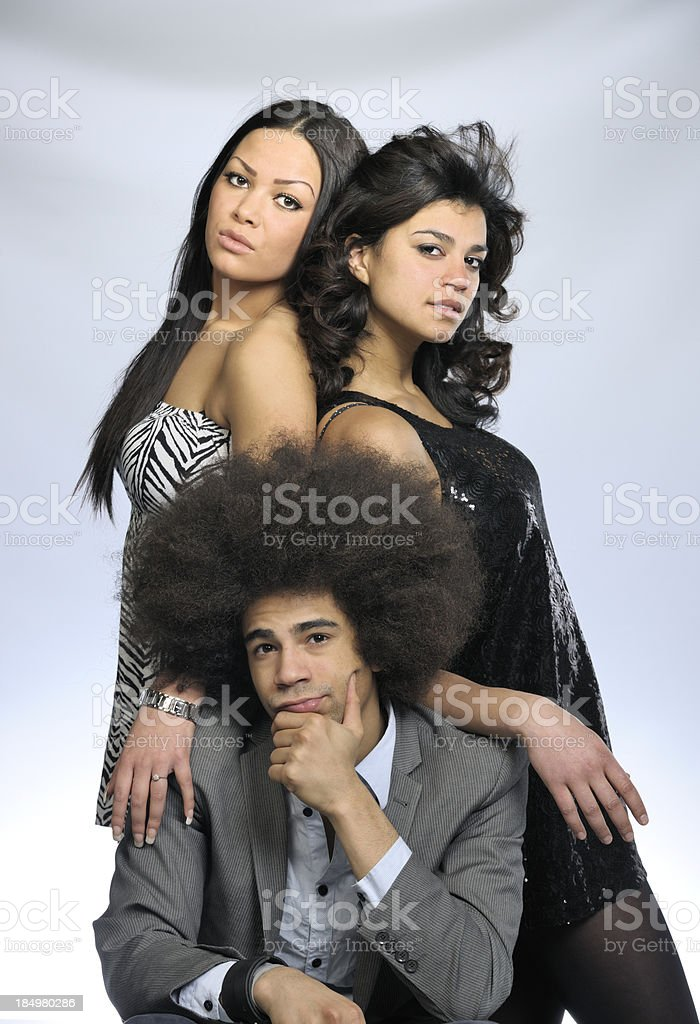 two attractive women leaning on kneeling cool man stock photo