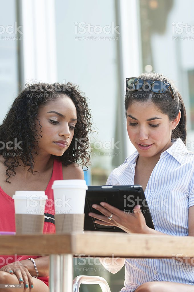 Two Attractive Women Viewing Computer Tablet royalty-free stock photo