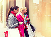 Two attractive young female friends enjoying a day out shopping
