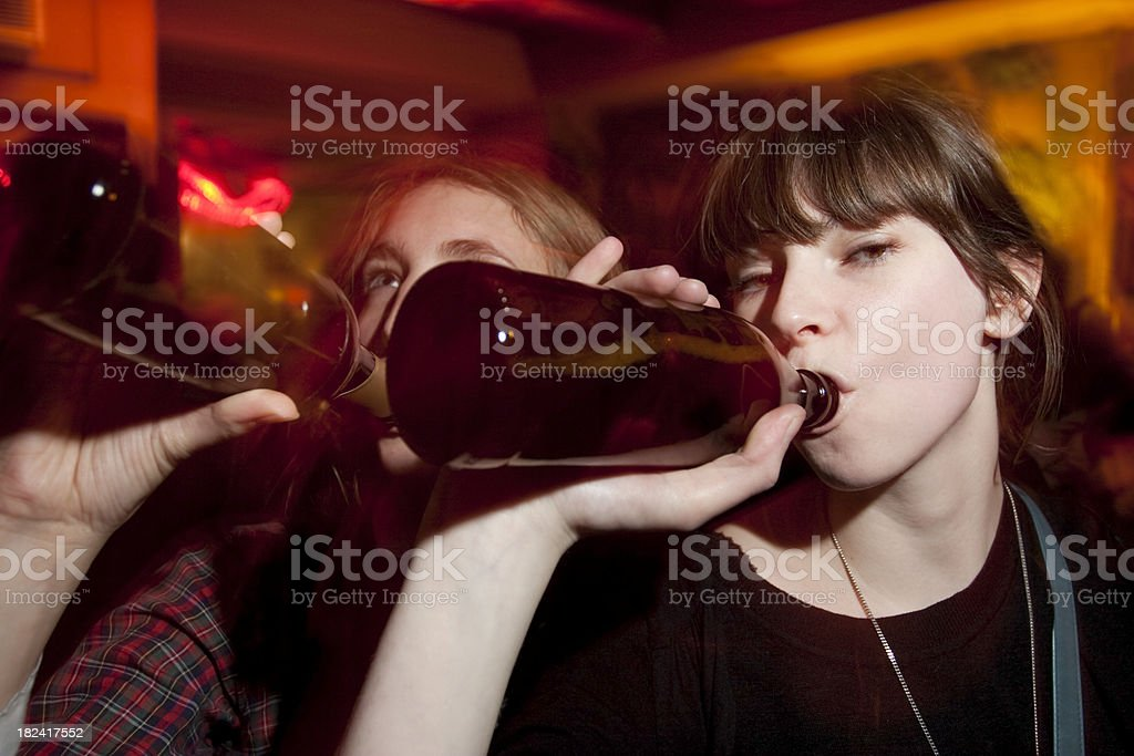 Two Attractive Young Women Drinking Beers at a Bar stock photo