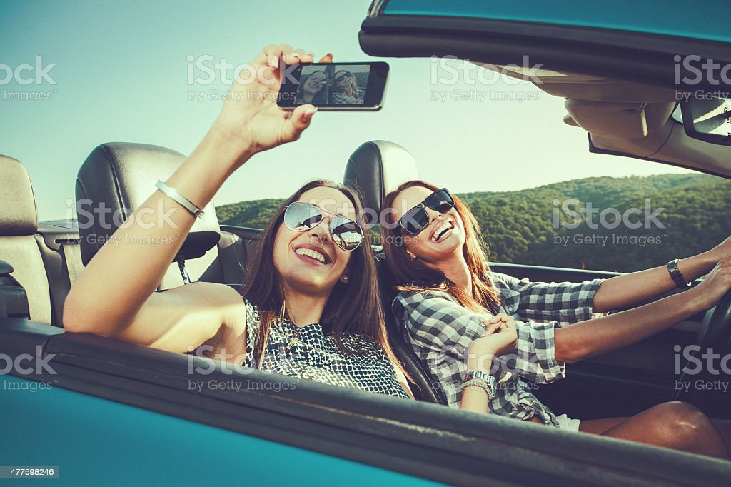 Two attractive young women dtaking selfe in a convertible car stock photo