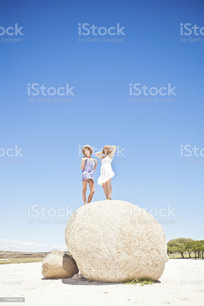 Two attractive young women standing on a boulder stock photo