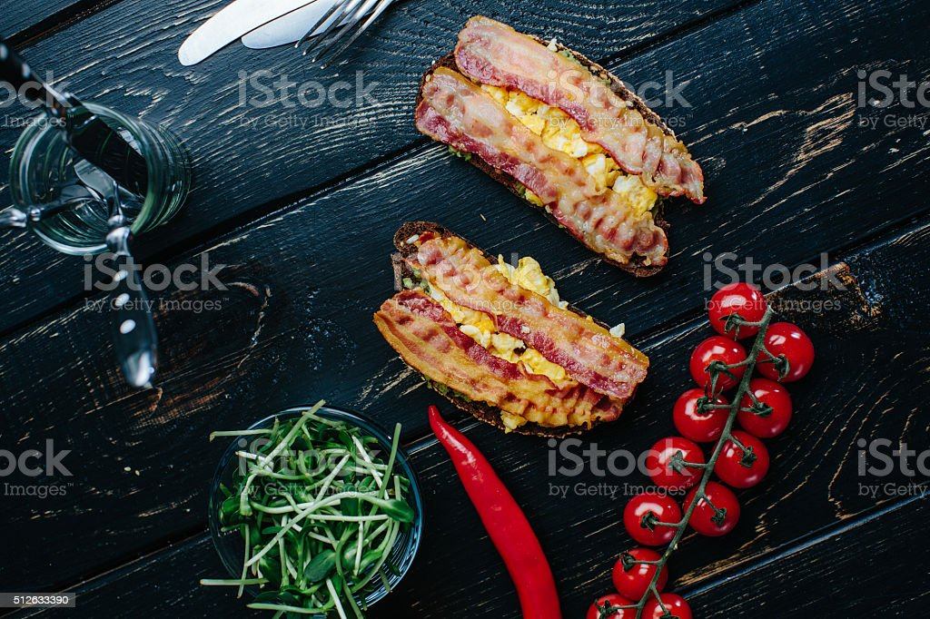 Two avocado and bacon toasts lying on a table stock photo