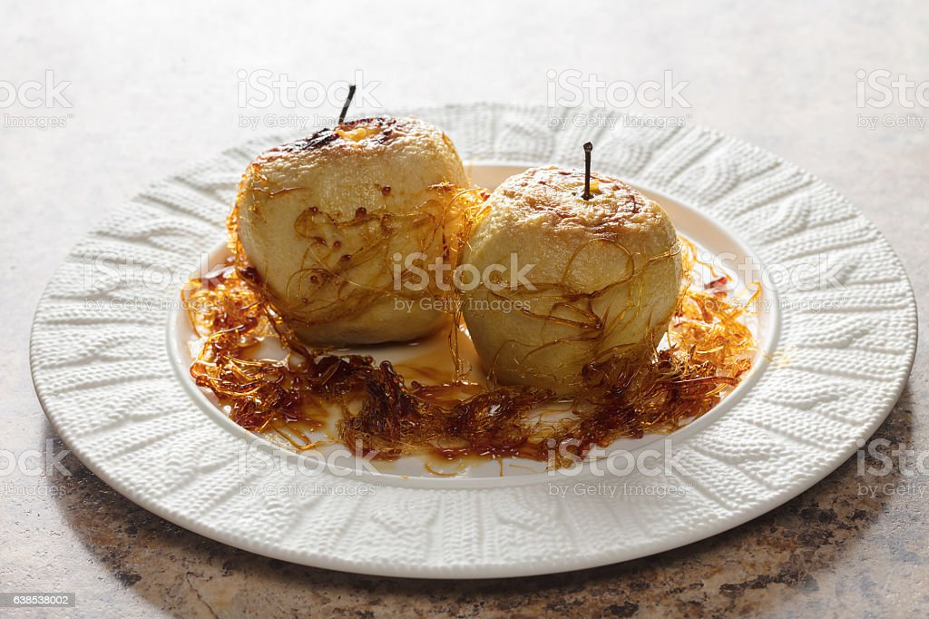 two baked apples with caramel stock photo