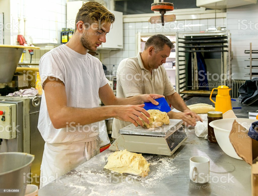 two Bakers preparing bread for the oven. stock photo
