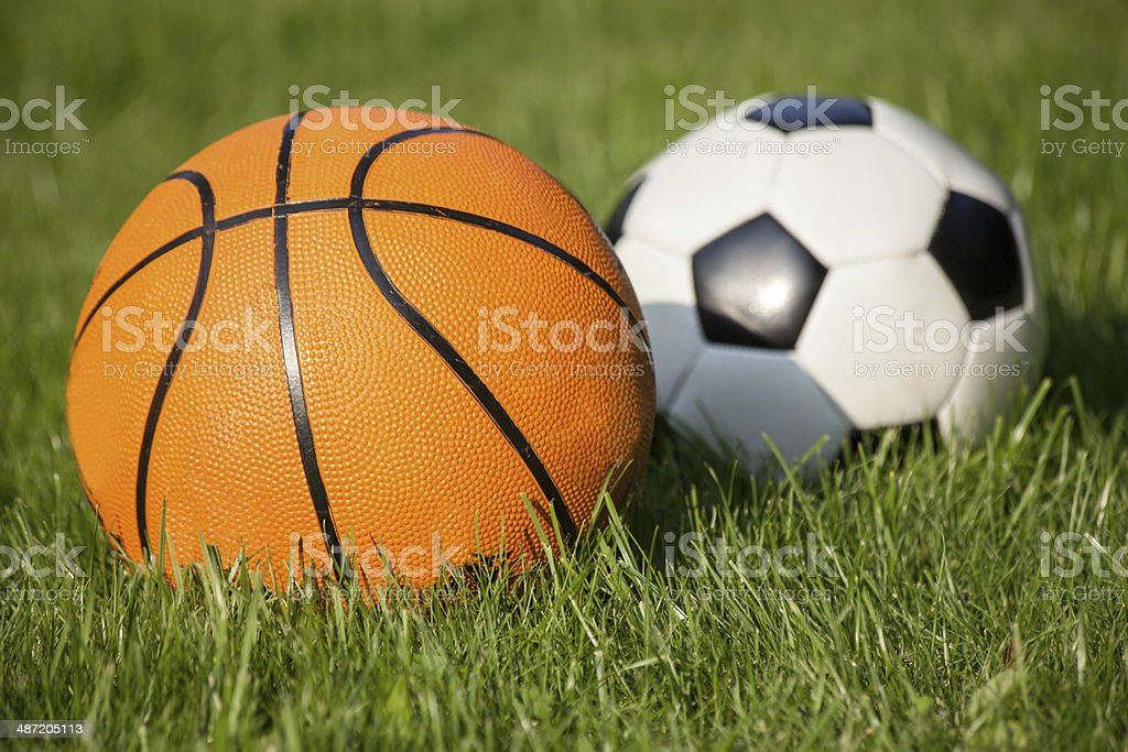 Two balls in the grass representing two sports - basketball and...