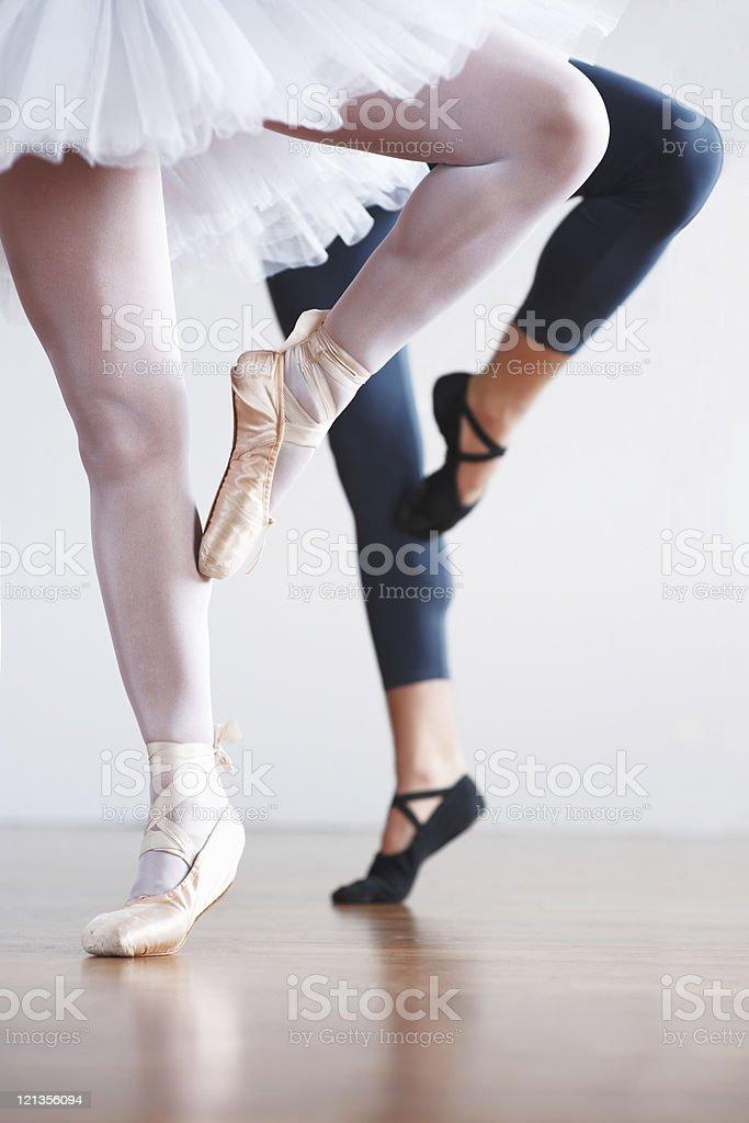 Two ballet dancer's legs practicing on floor stock photo