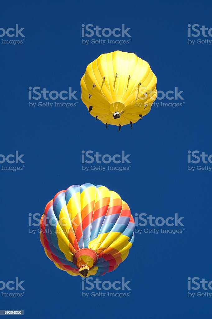 Two balloons sailing off into a deep blue sky royalty-free stock photo
