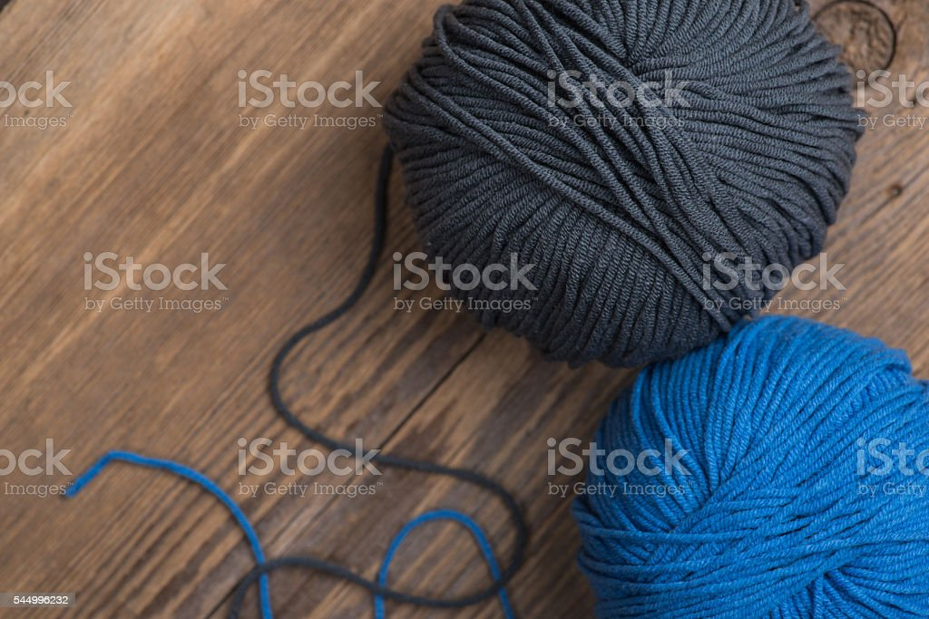 Two balls of knitting yarn on wooden surface stock photo