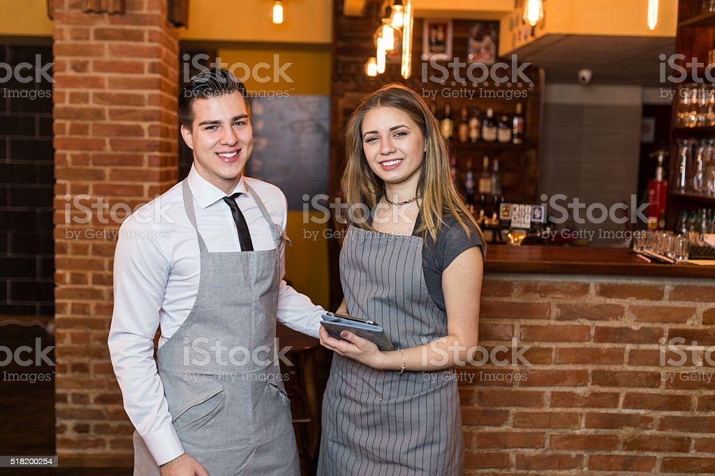 Two baristas smiling at the camera at the cafe stock photo