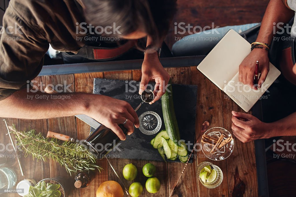 Two barmen creating new cocktail recipe stock photo
