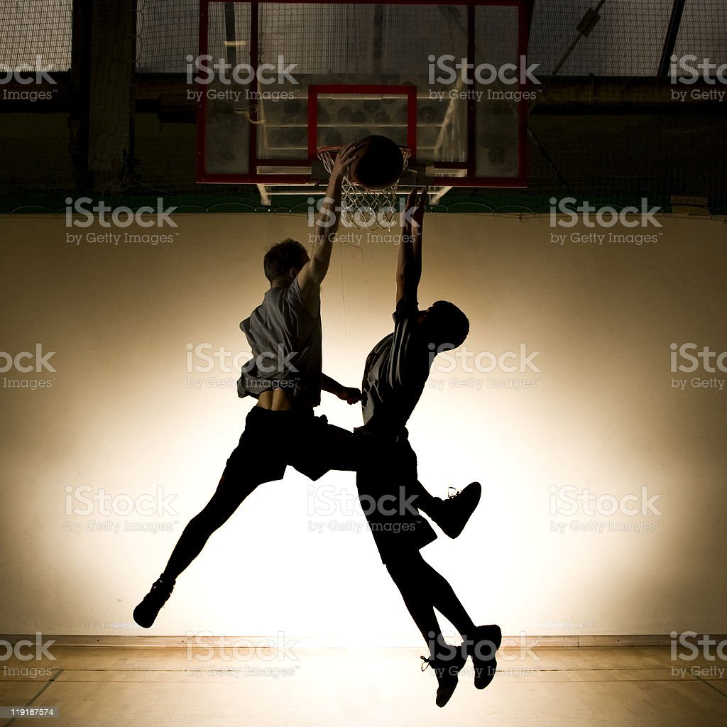 Two basketball players jumping to the ball stock photo
