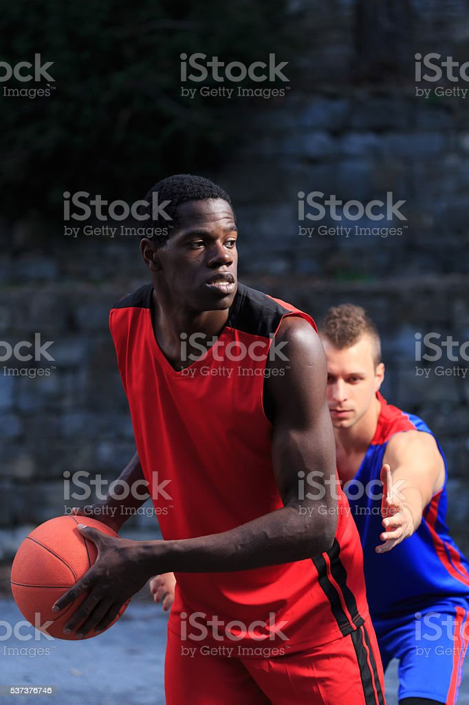 Two basketball players on dark background stock photo