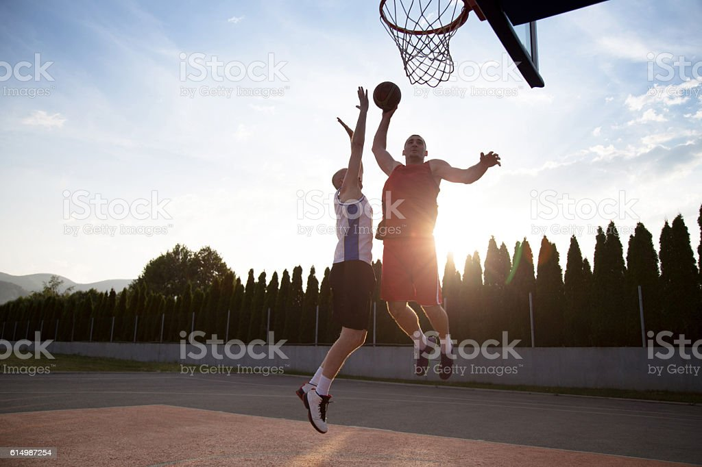 Two basketball players on the court outdoor stock photo