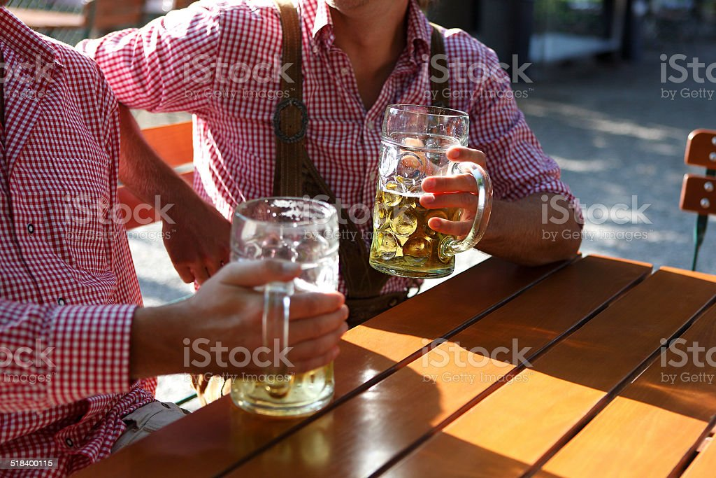 Two Bavarians sitting in a beer garden stock photo