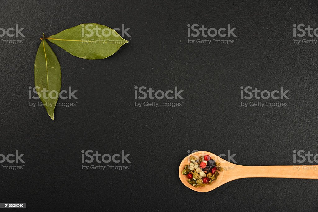 Two bay leaves and pepper on black chalkboard royalty-free stock photo