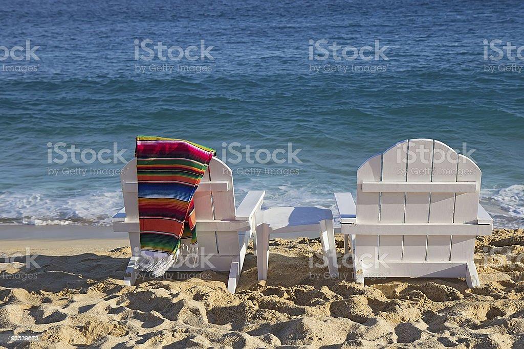 Two beach chairs near ocean stock photo