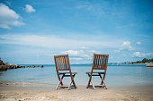 Two beach chairs on tropical shore