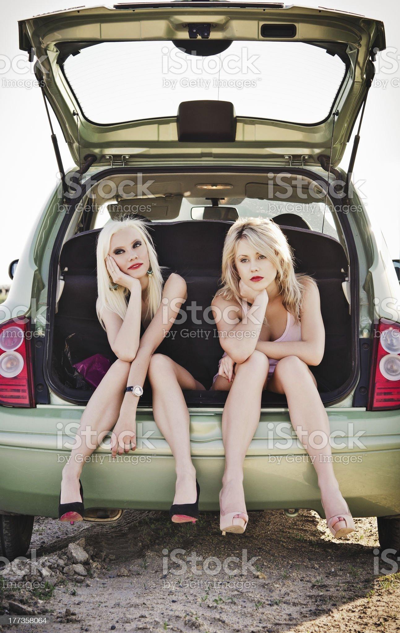 Two beautiful blonde girls sitting in trunk of broken car royalty-free stock photo