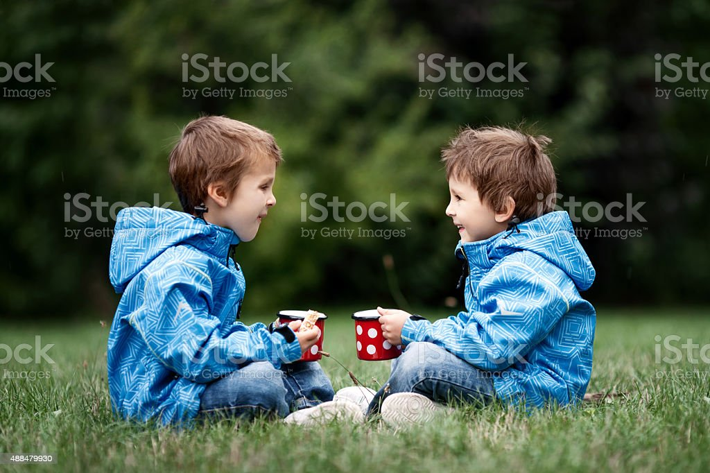 Two beautiful boys, brothers, sitting on a lawn, autumn time stock photo