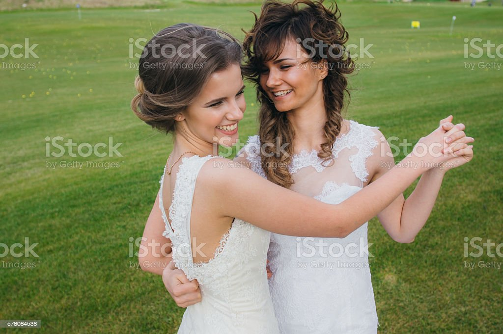 Two beautiful brides dancing on the green field stock photo